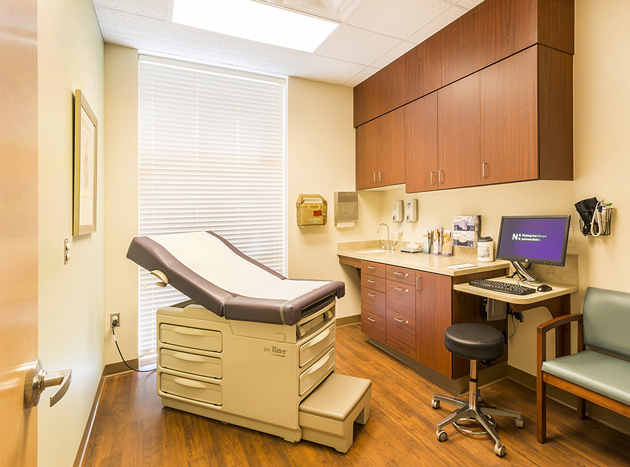The exam rooms of Triad Plastic Surgery feature floor to cieling windows and hardwood floors.